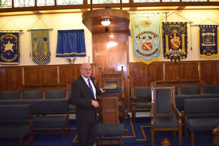 Assistant provincial grand master of the West Lancashire Freemasons David Grainger stands in front of decorative banners representing some of the local group's Lodges